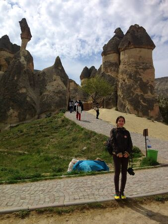 Woman standing near the rock formation turkey  Stock Photo