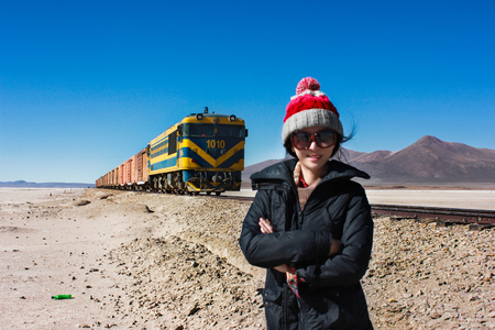 woman standing while the train pass behind Editorial