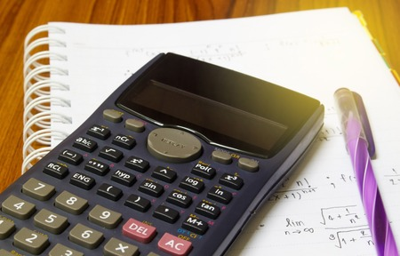 Maths concept - handheld calculator on a sheet of paper with maths-formulas
