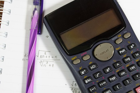 axiom: Maths concept - handheld calculator on a sheet of paper with maths-formulas