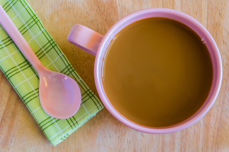 Hot coffee in pink cup and spoon on cloth Imagens