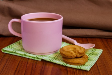 Hot coffee in pink cup with cookies and spoon on cloth