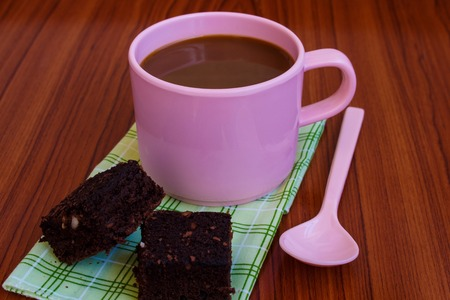Hot coffee in pink cup with brownie and spoon on cloth Imagens