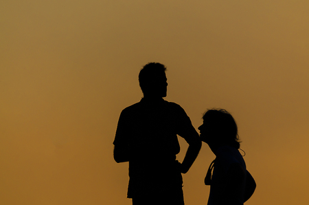 two people with others: Silhouette couple talking