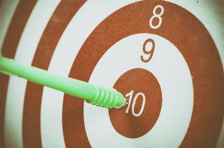 cir: Green dart arrow hitting in the target center of dartboard
