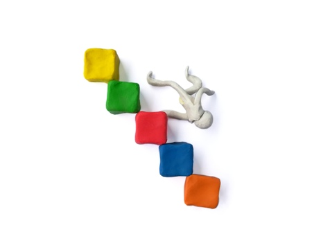 Plasticine clay made blocks stacked staircase,person falling down the stairs,on white background.Its like a most successful business,but make some mistakes can cause serious damage.So be very careful Stock Photo