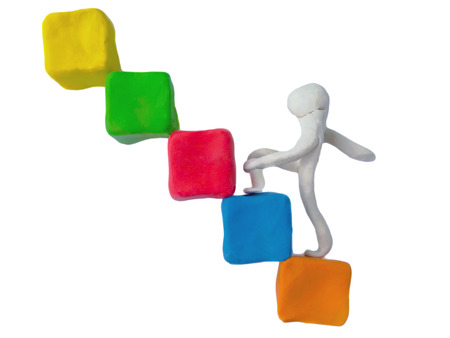 Clay plasticine clay stacked squares are staircase and there are people stepping up on a white background,like a beginner business,Stepping things in order to reach the goal,This may take a short or long