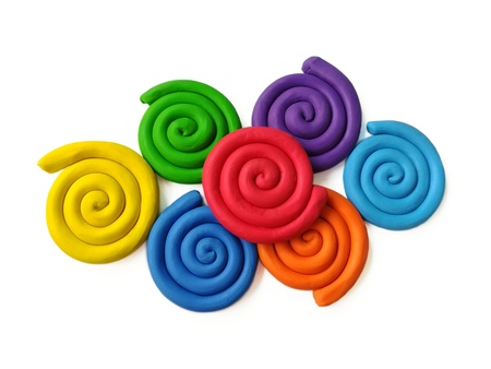 Colorful plasticine clay are curled into a spiral placed on white background,cute rainbow colored dough
