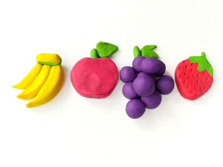 Delicious fruits (banana, apple, grapes, strawberry) made from plasticine clay dough arrange line placed on white background Archivio Fotografico