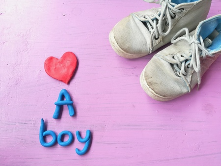 Plasticine clay dough made are cute red heart, blue a boy text and boys sneakers on pink background,  lovely wallpaper Stock Photo