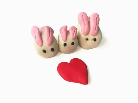 Sweetie color clay plasticine made are beautiful rabbits family and lovely hearts placed on white background, cute animal dough Stock Photo