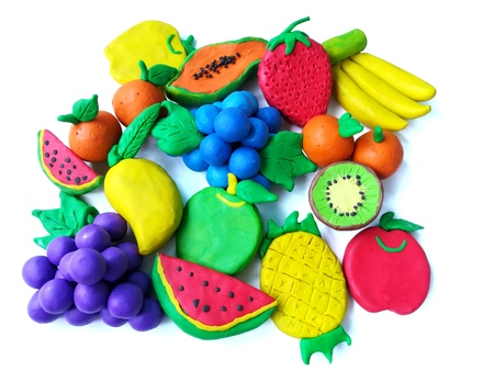 Colorful clay plasticine made are variety fruits on white background, delicious watermelon kiwi pineapple grapes papaya apple blueberry banana mango orange strawberry dough