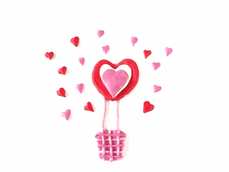 Beautiful balloon and red pink heart made from plasticine clay on white background, lovely pattern dough