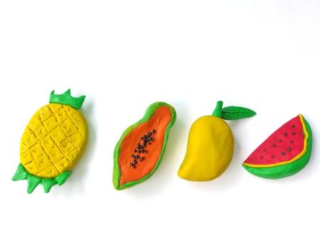 Delicious variety fruit handmade from plasticine clay on white background, colorful cute pineapple banana mango watermelon shape dough 版權商用圖片