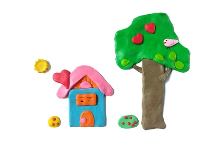 Home sweet home made from colorful plasticine clay on white background, tree flower and cute bird are beautiful view dough 免版税图像