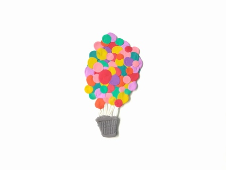 Balloon baskets decorated with colorful balloon made from plasticine clay floating up into the sky are beautiful placed on white background, cute shaped are dough