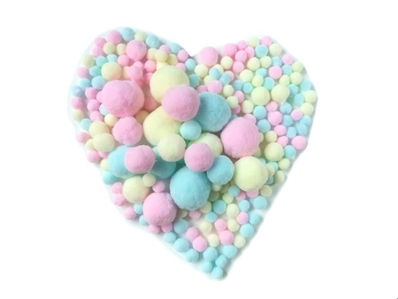 Variety size colorful pom pom made from fiber arrange beautiful heart shape on white background, Big and small cute pastel balls