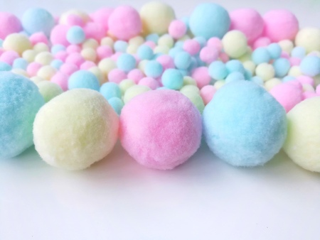 Beautiful pastel pom poms made from colorful fiber yarn, large pieces arrange line horizontal next back with a smaller than closed at the end with medium size are all placed on white background
