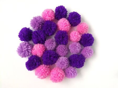 Pink and purple colored pom pom yarn arrange circle shape on white background