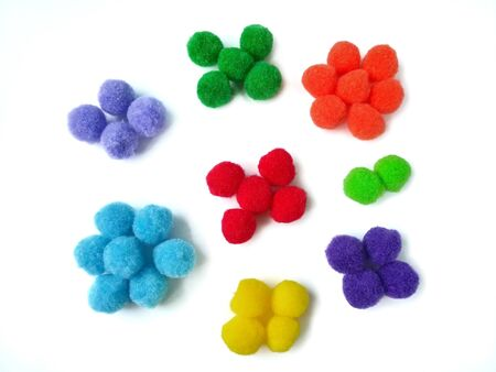 Colorful pom pom arranged in groups of colors placed on white background