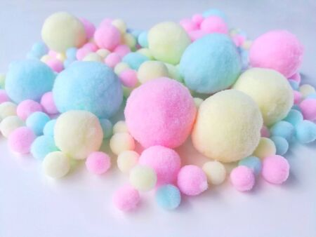 Variety size colorful pom pom made from fiber placed on white background, Big and small cute pastel balls