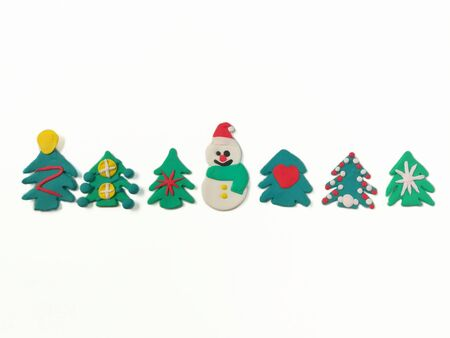 Cute snowman have sweet smile, colorful ornaments on Christmas tree are made from plasticine clay are placed on white background, beautiful dough decorate are festival