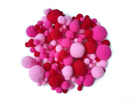 Variety size pom pom made from pink and red fiber yarn arranged circle on white background