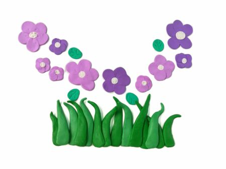 Beautiful purple flowers on green grasses handmade from plasticine clay are on white background, cute shape natural are dough