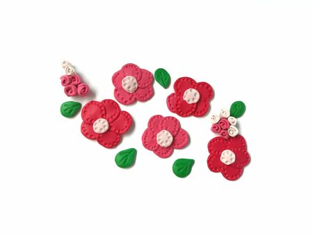 Beautiful red flowers and green leaves handmade from plasticine clay are on white background, cute shape natural are dough Reklamní fotografie