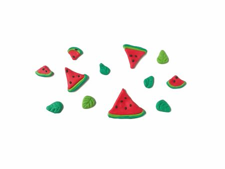 Delicious red watermelon slice and green leaf made from plasticine clay decorate are beautiful pattern on white background, cute different size fruit piece dough