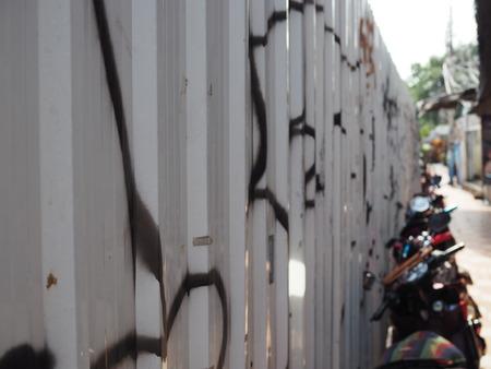 Grafiti 黒汚いスプレー、セメント床路地の横にある駐車場をスタッキング バイク段亜鉛金属灰色鉄フェンス壁