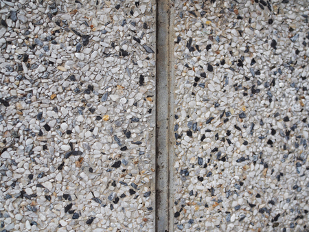 grooves: Old dirty grainy small white black stone texture pattern wall surface background with vertical groove cement line