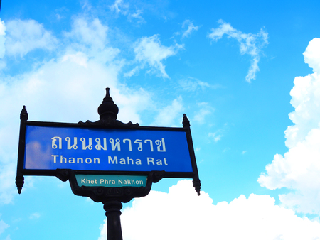 "Bangkok, Thailand - October 17, 2017: Shiny traditional road sign post of "" Thanon Maha Rat"" both in Thai and English text language, close up perspective shot, with light blue sky and white clouds Editorial"