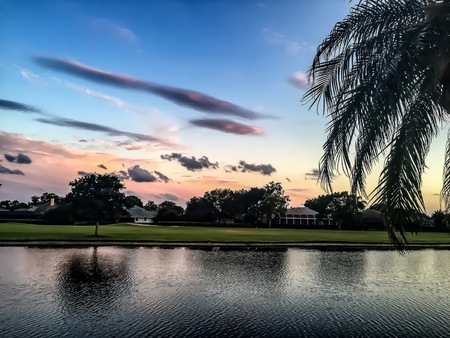 setting sun on a golf course with palm trees Stock Photo