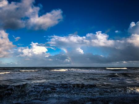 クラッシュの波と海の嵐の後の虹