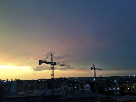 cranes on the roof of a city skyline
