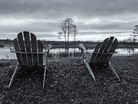 wooden chairs on the levee looking at sunset in the marsh