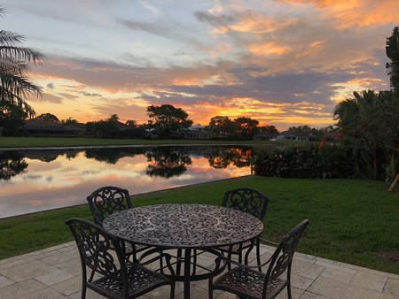 colorful sunset in the tropical back yard and patio furniture