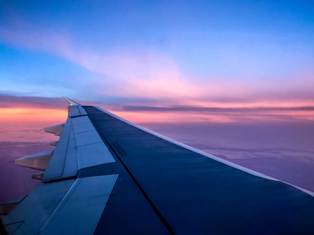 aerial sunrise over airplane wing in flight Stock Photo