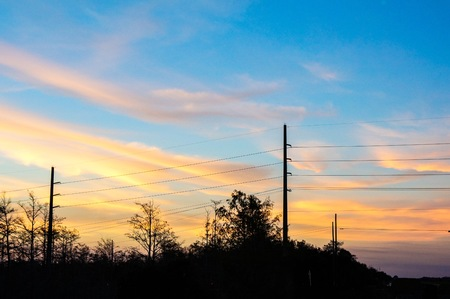 sunset sky and silhouette of power lines in the country