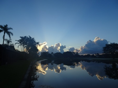 palm tree silhouettes reflecting in a lake and in a sunset sky Stock Photo