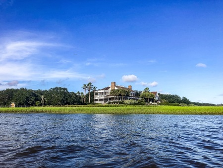 Beautiful summer day on Shem's Creek looking at Southern white mansion and the swamp