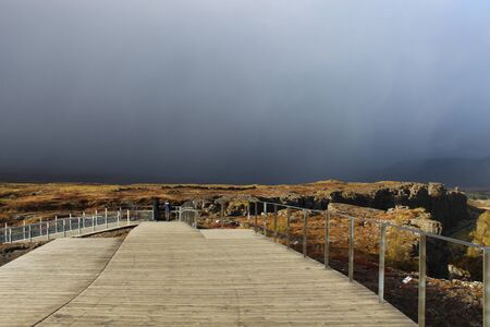 Golden Circle, Iceland -hazy sun through storm clouds at the boardwalk of Thingvellir National Park in Iceland