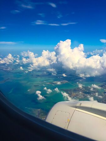 turquoise ocean and beautiful puffy white clouds welcomes vacationer to the island