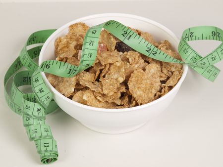 wild oats: Measurement tape wrapped around dish with flakesConcept for health, diet Stock Photo