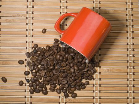 overturn: Cup with coffee  and  coffee grain