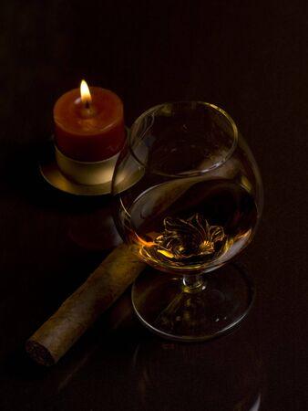 Glas mit Getr�nk, Zigarren und Kerze auf einem dunklen Hintergrund
