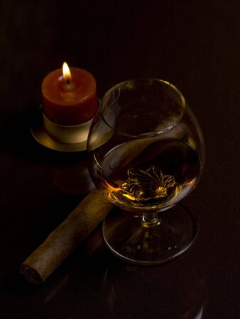 Glass with drink, cigar and candle on a dark background photo