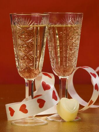 two glasses with wine on a red background
