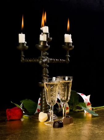 Candles, glasses with wine, rose on a black background photo